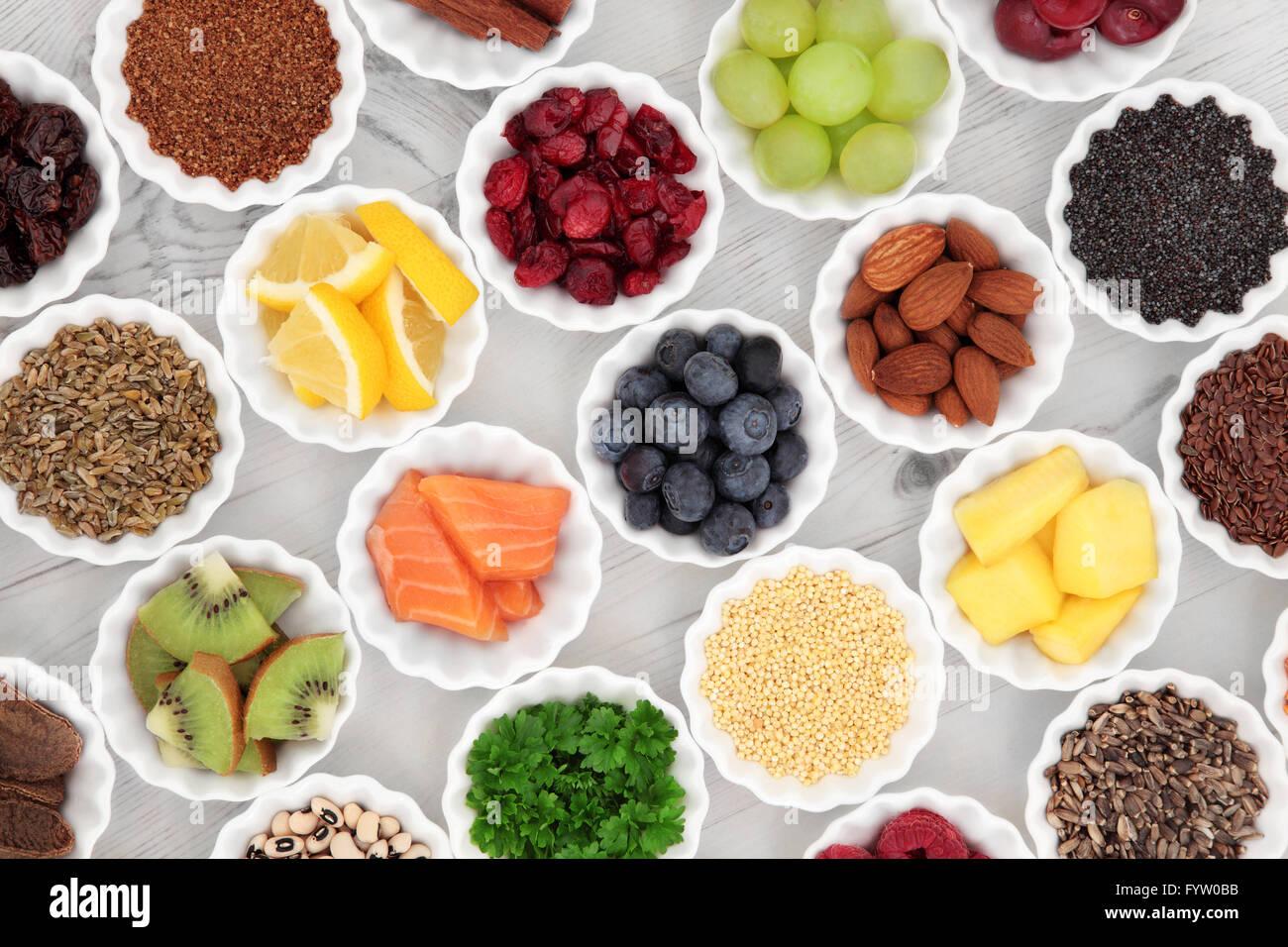 Super food selection in porcelain crinkle bowls over distressed wooden background. - Stock Image