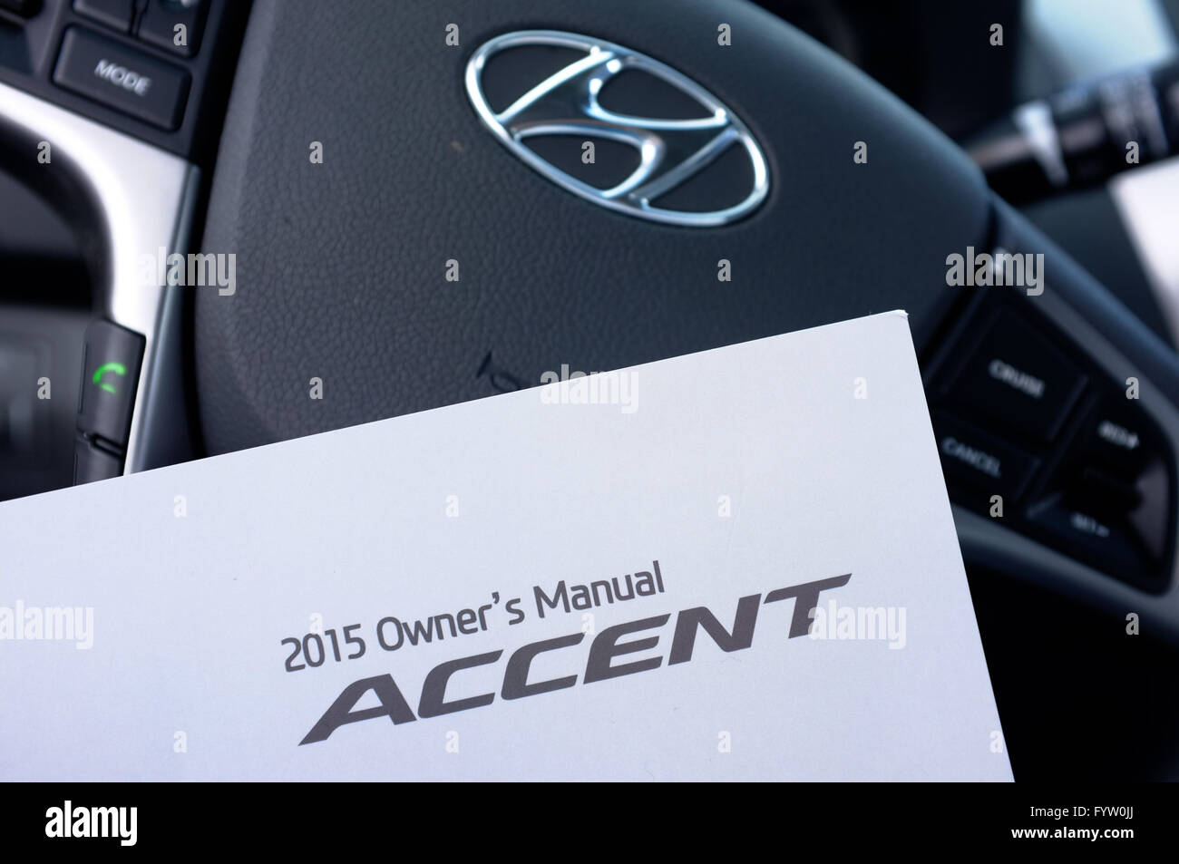 A Hyundai Accent Owner's Manual in front of a Hyundai steering wheel. -  Stock Image