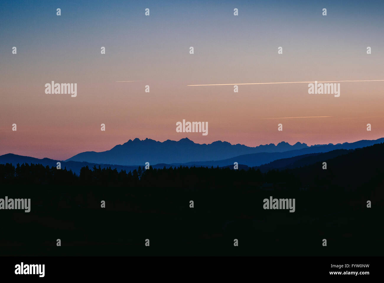 Plane trails above the Tatra mountains after sunset - Stock Image