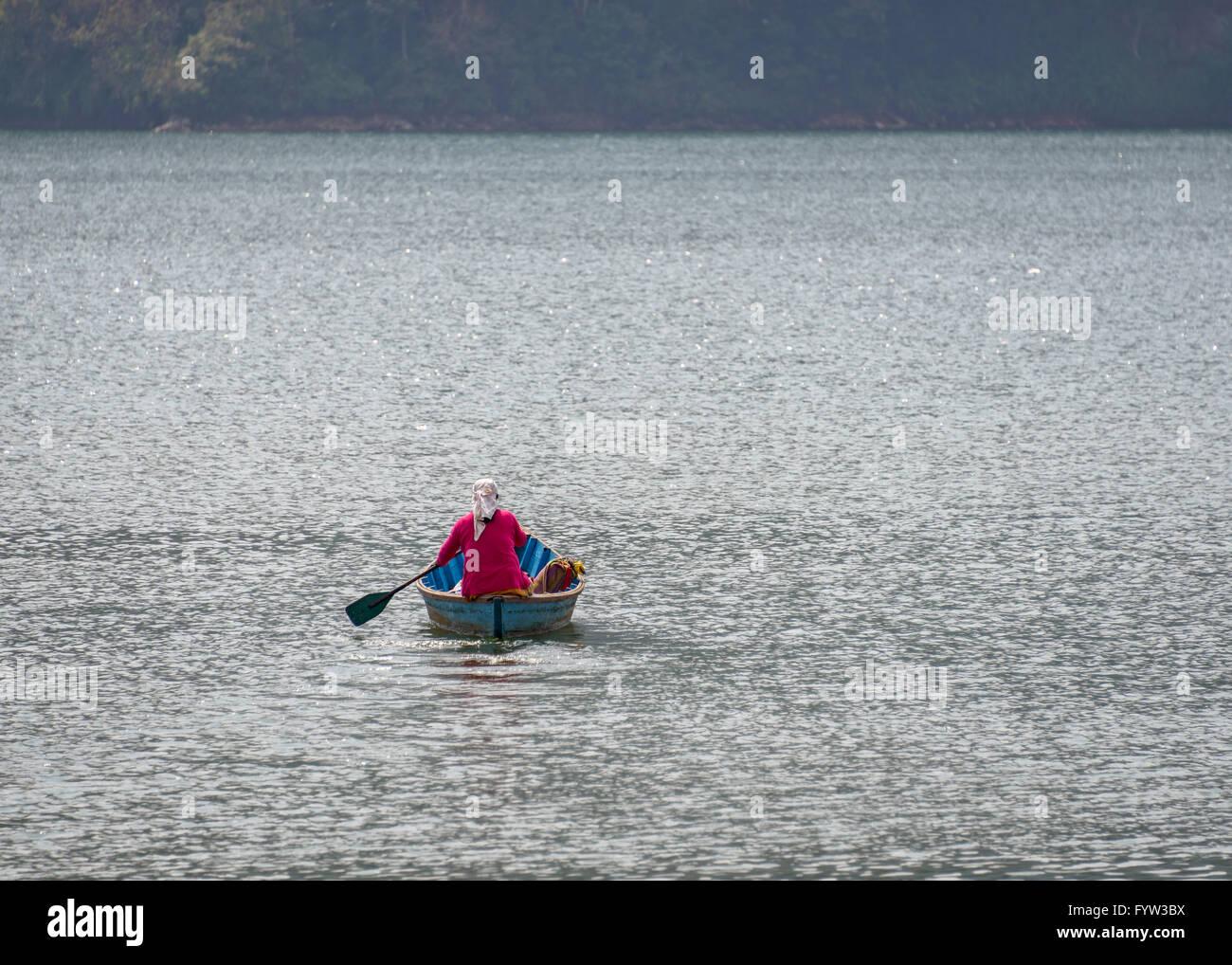 Nepalese woman paddling across Phewa Lake in Pokhara, Nepal - Stock Image