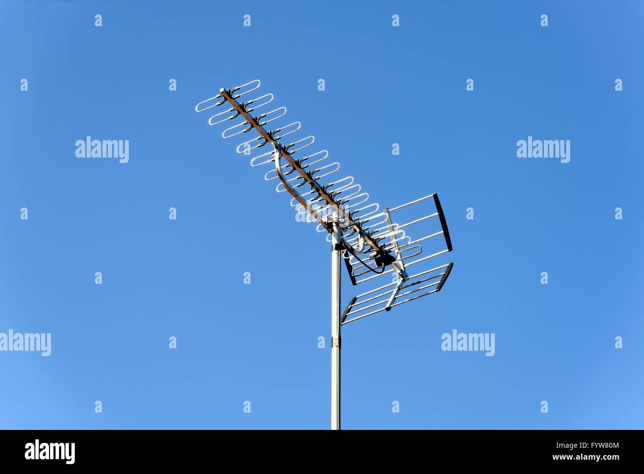Close up of a british television aerial against a blue sky - Stock Image