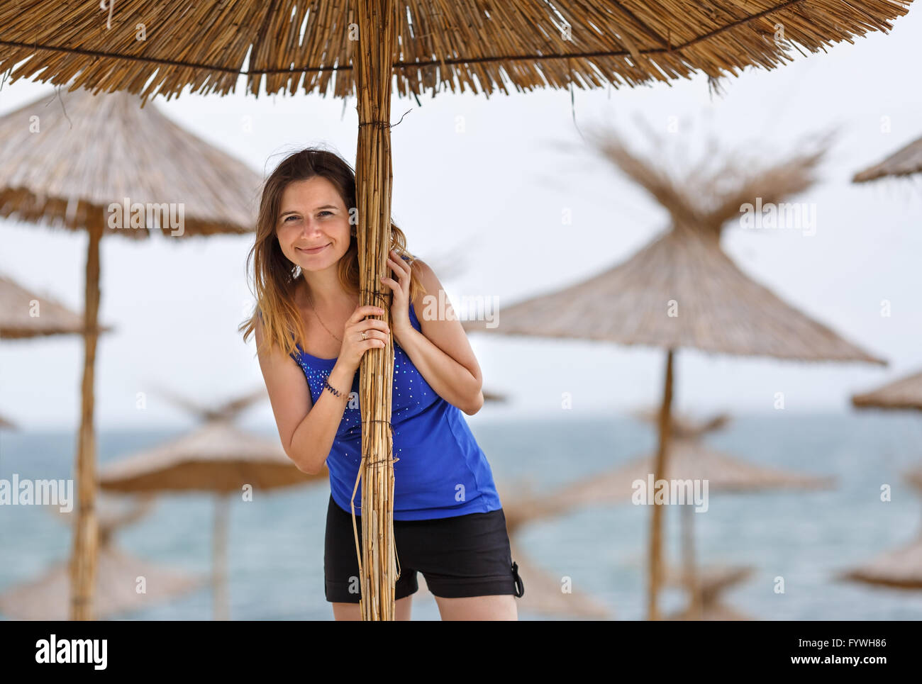 Woman and straw umbrella - Stock Image