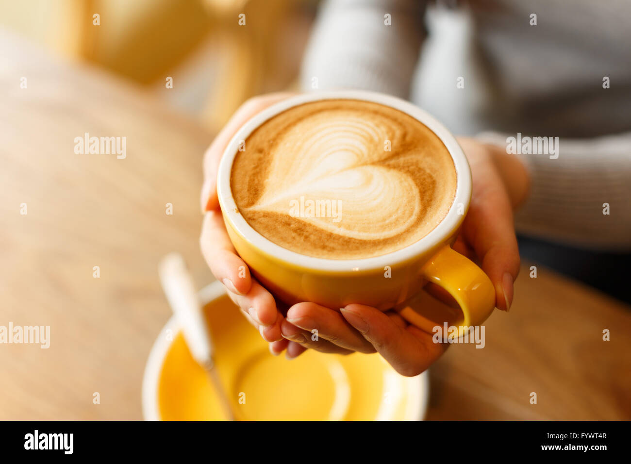lady's hands holding cup with sth heart-shaped - Stock Image