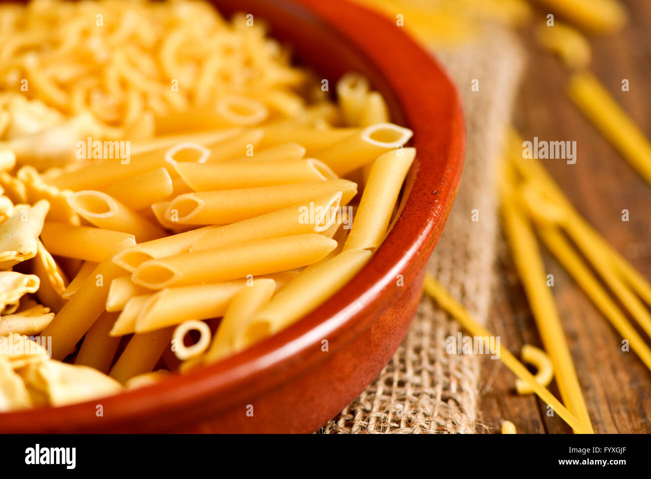 closeup of an earthenware bowl with different uncooked pasta such as ravioli, spaghetti or mostaccioli, on a rustic Stock Photo