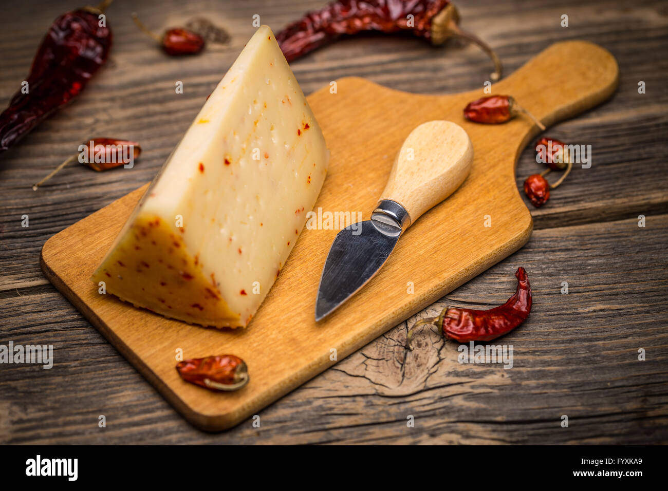 Piece of artisan cheese with chilli on wooden cutting board - Stock Image