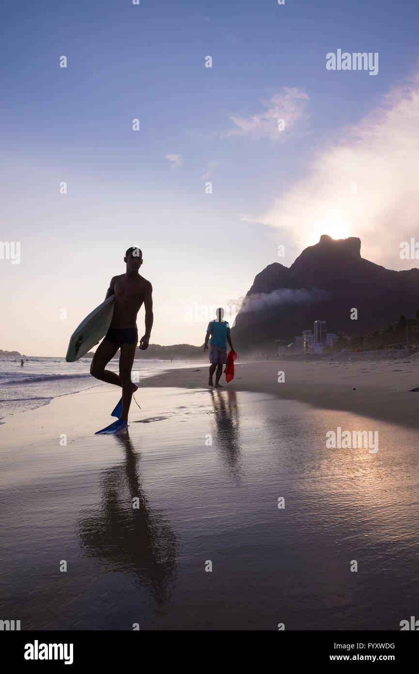 RIO DE JANEIRO - MARCH 8, 2016: Bodyboarders walk on São Conrado Beach under a sunset silhouette of the iconic - Stock Image