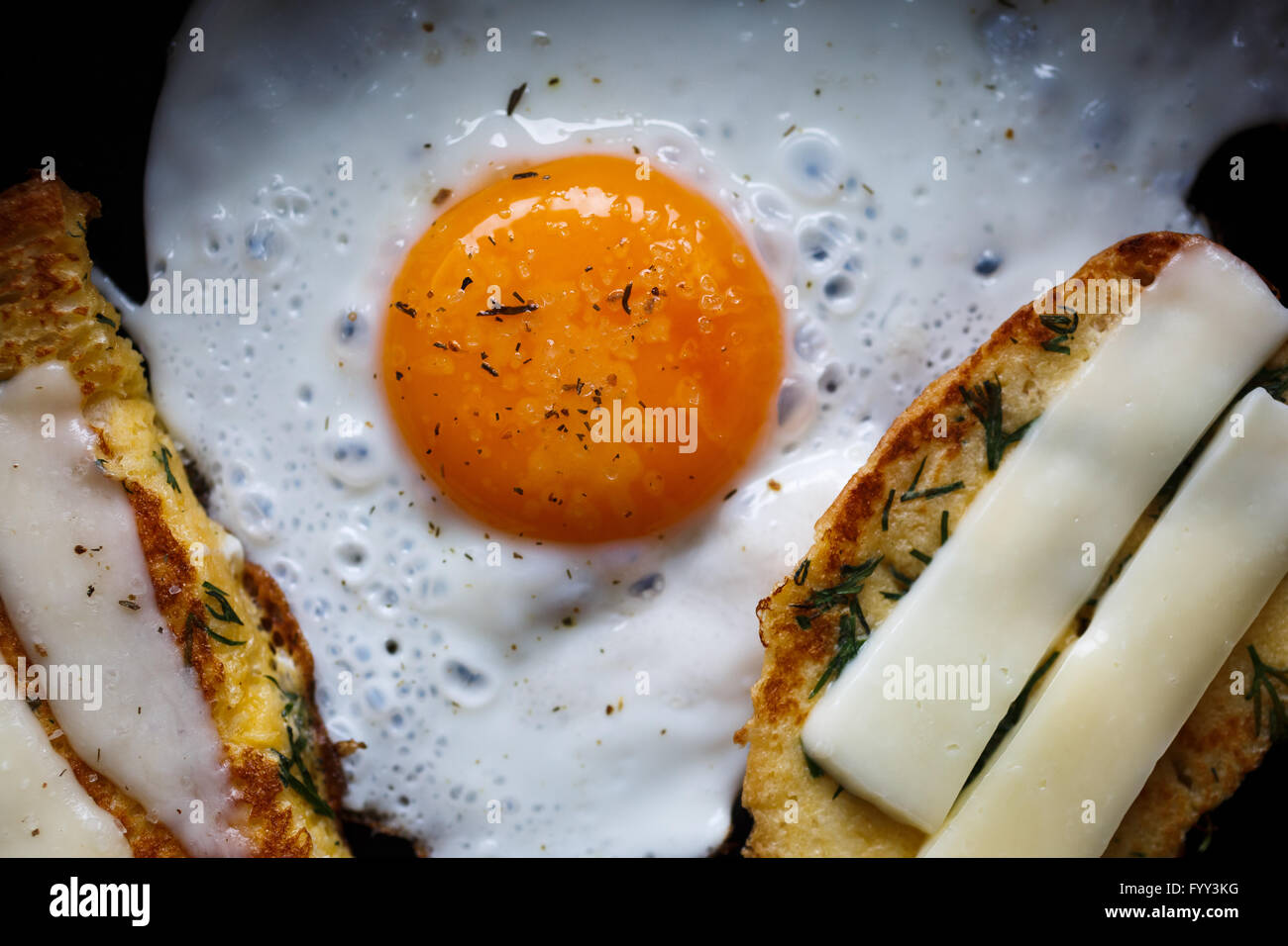 fried egg and bread with cheese - Stock Image