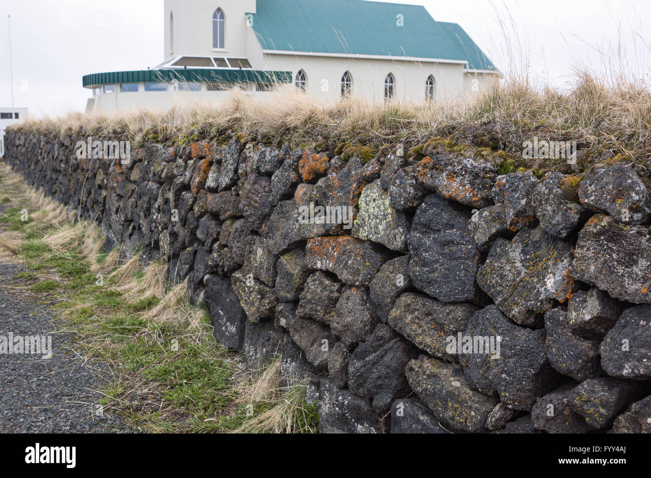 Rock wall with church behind, Iceland - Stock Image