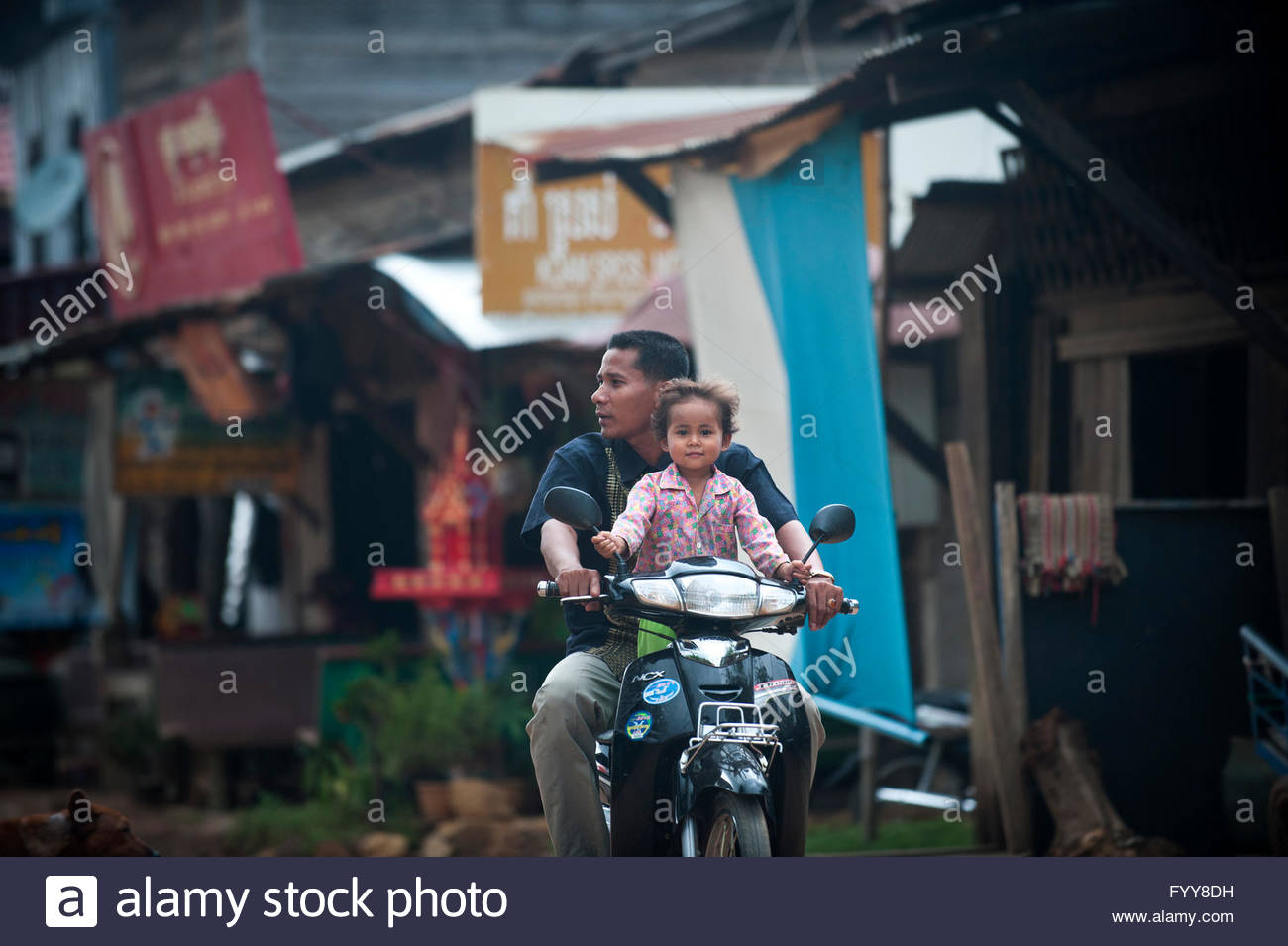 Father and daughter ride their motorbike through Banteay Chhmar, Cambodia. - Stock Image