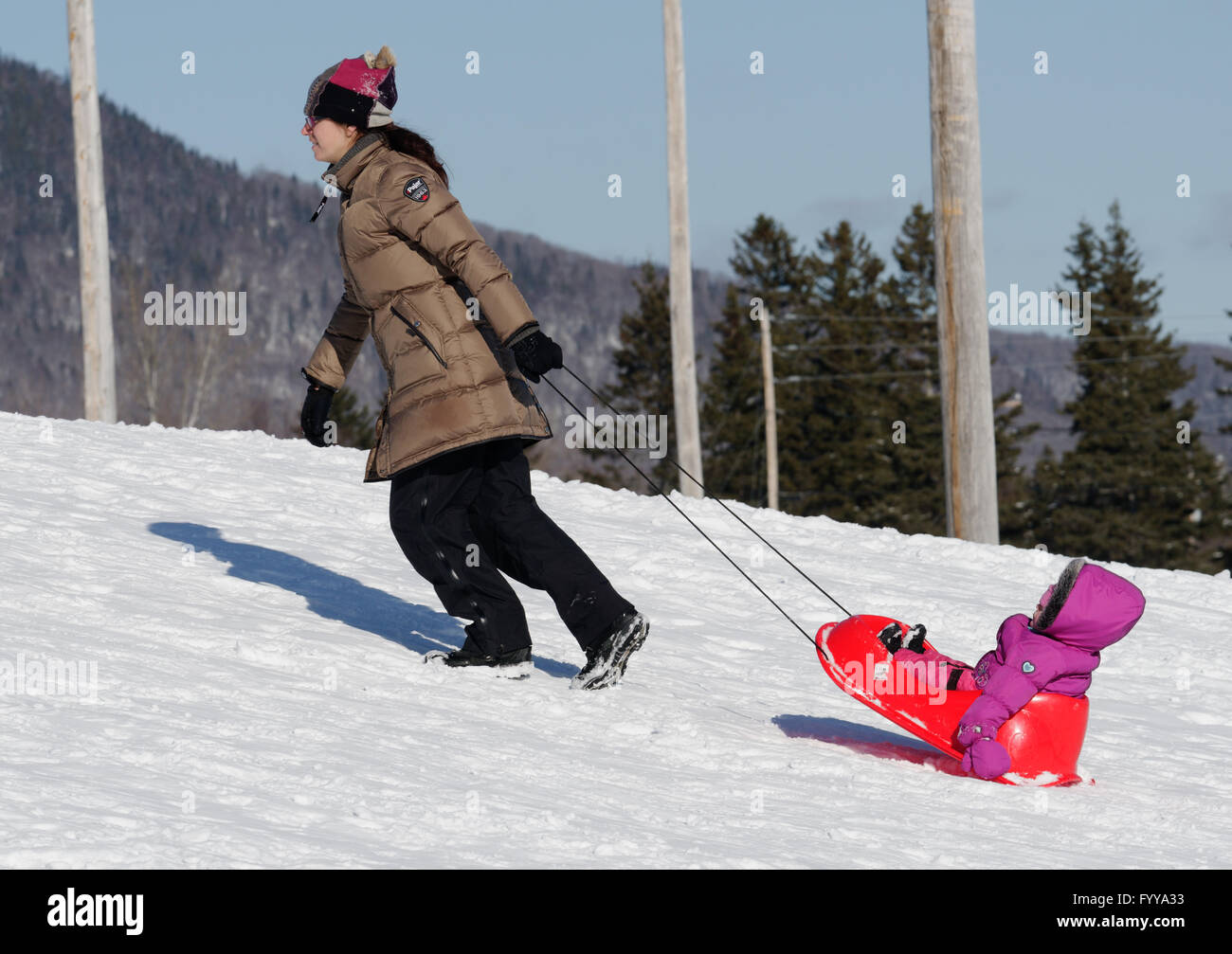 A mum pulling a little girl in a sledge - Stock Image