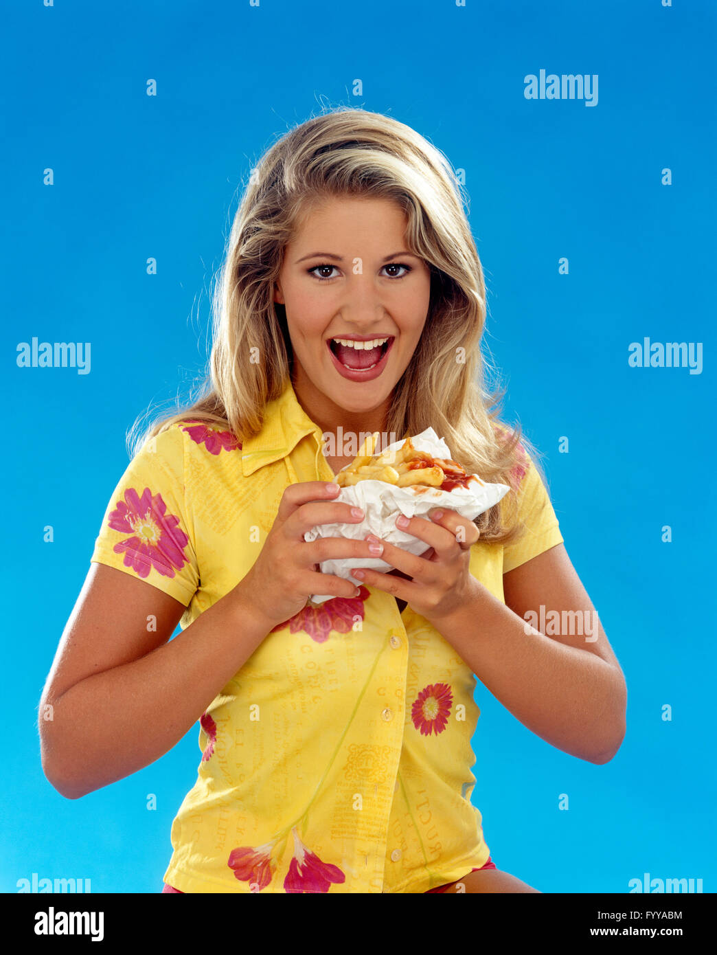 Girl eating a chip butty, British classic, indoors. - Stock Image