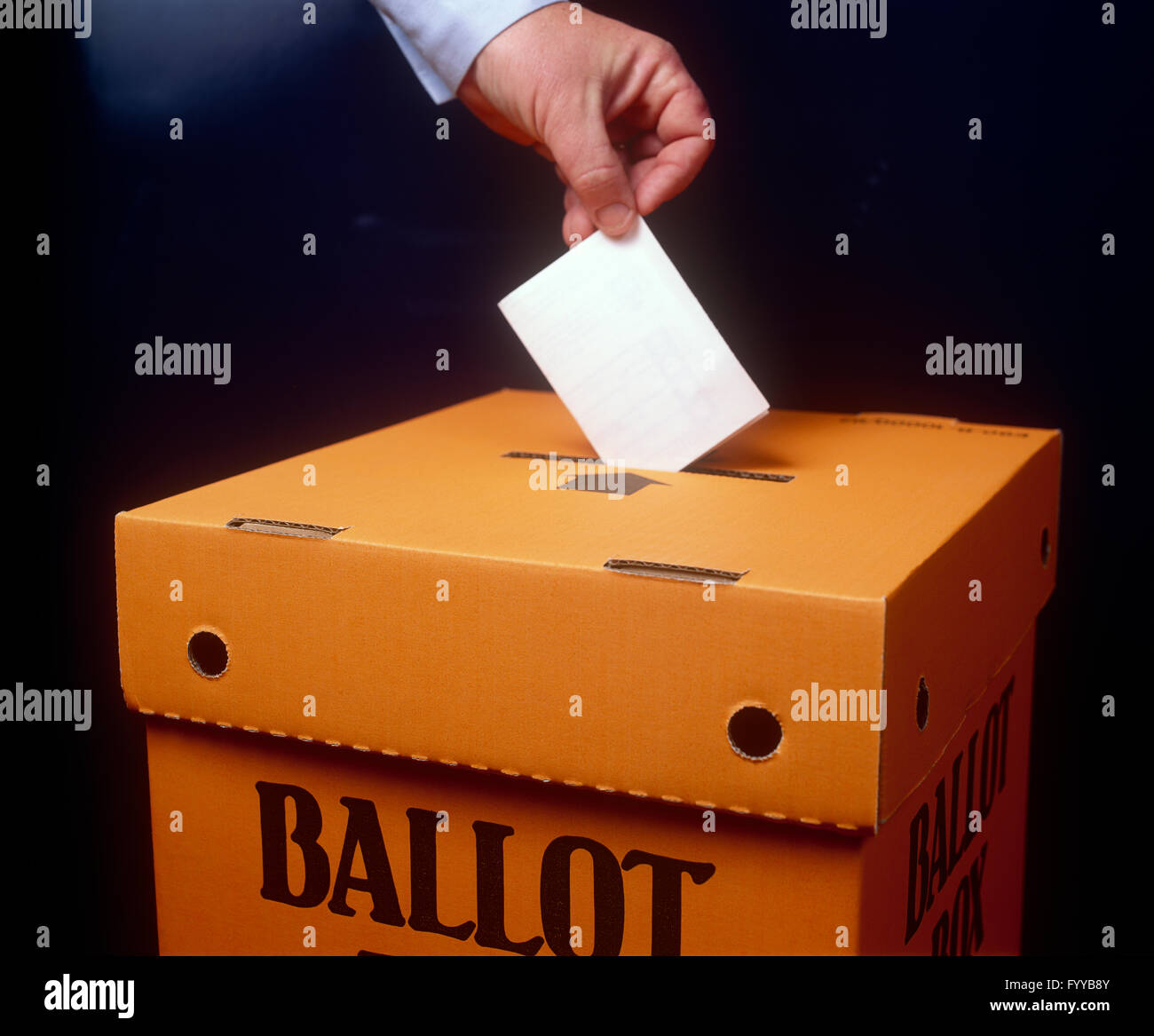 Voting paper being placed into a Ballot box, inside. - Stock Image