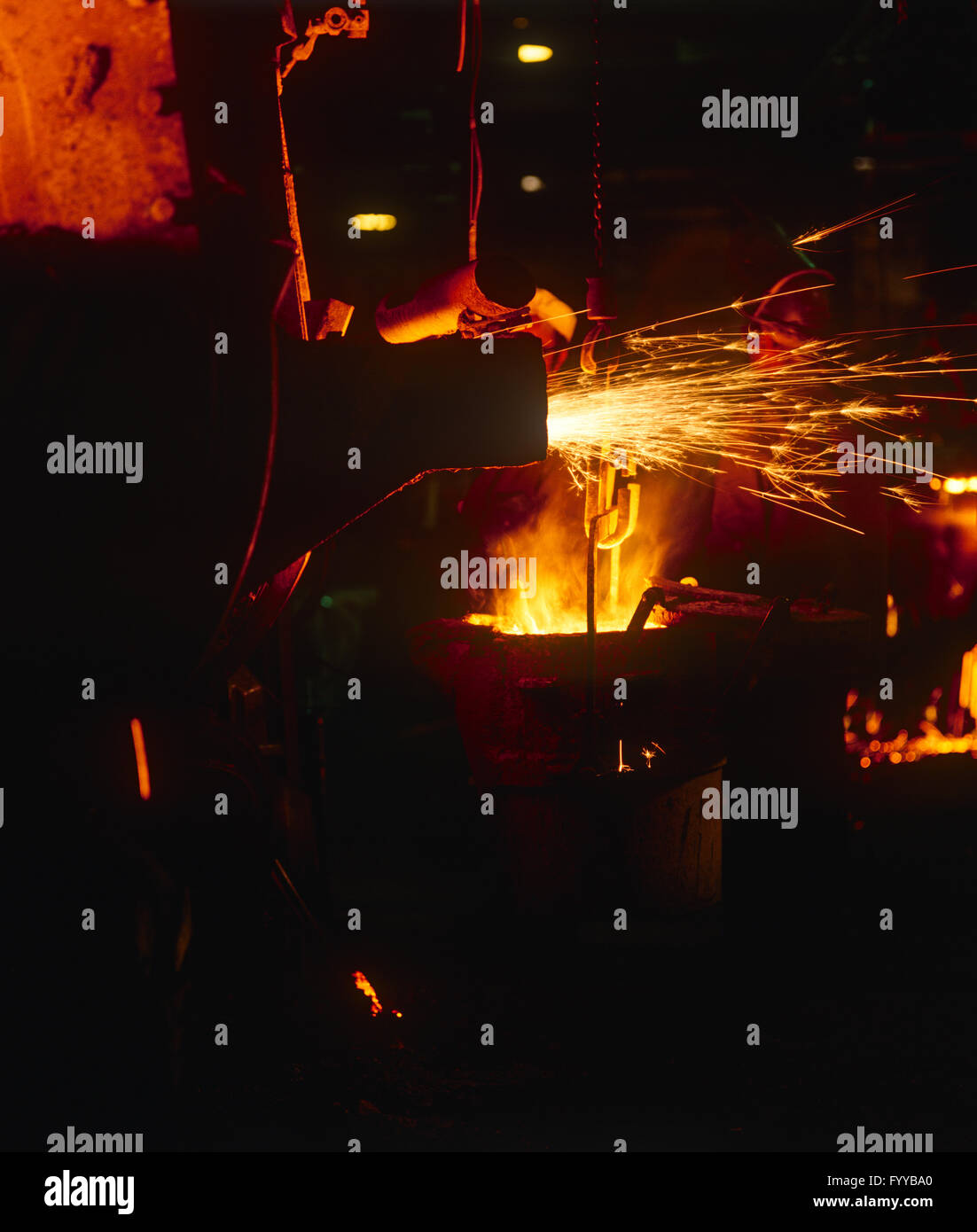 orange sparks from machinery, indoors. - Stock Image