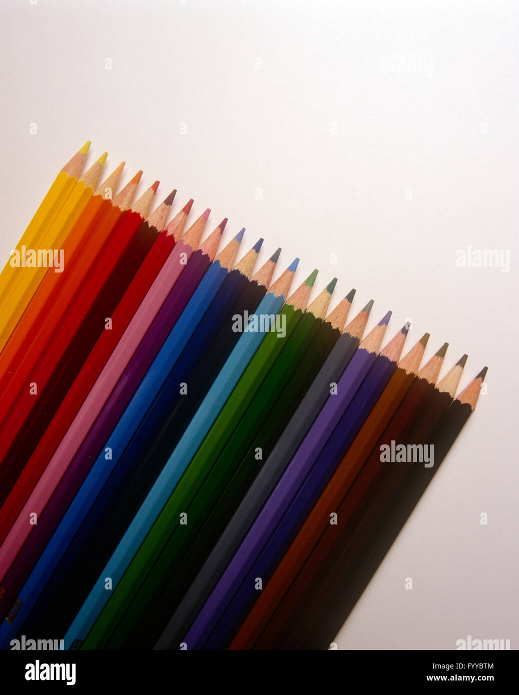 Multi-coloured pencils in a line, inside. - Stock Image