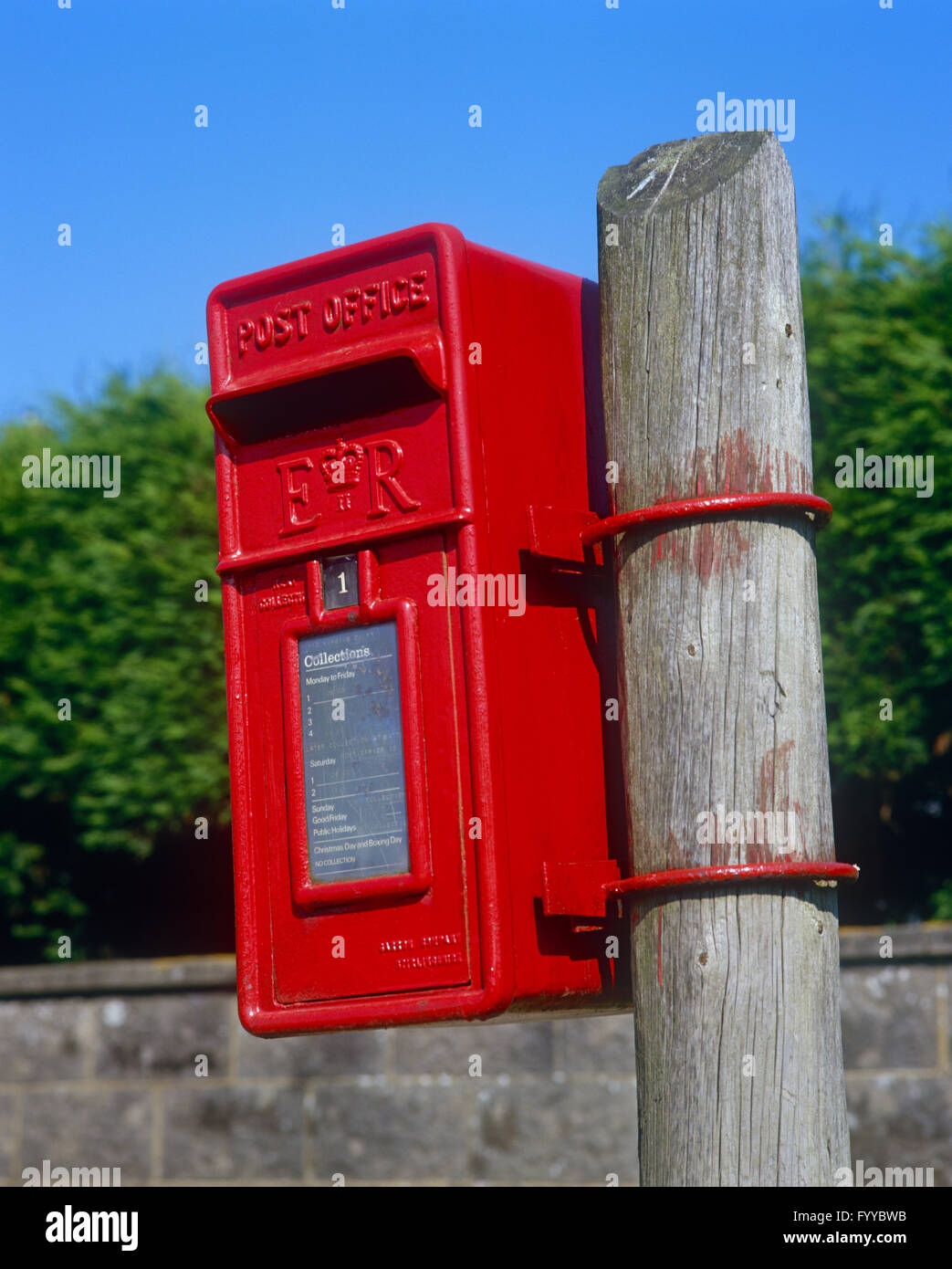 Red postbox on a wooden stick, outside. - Stock Image