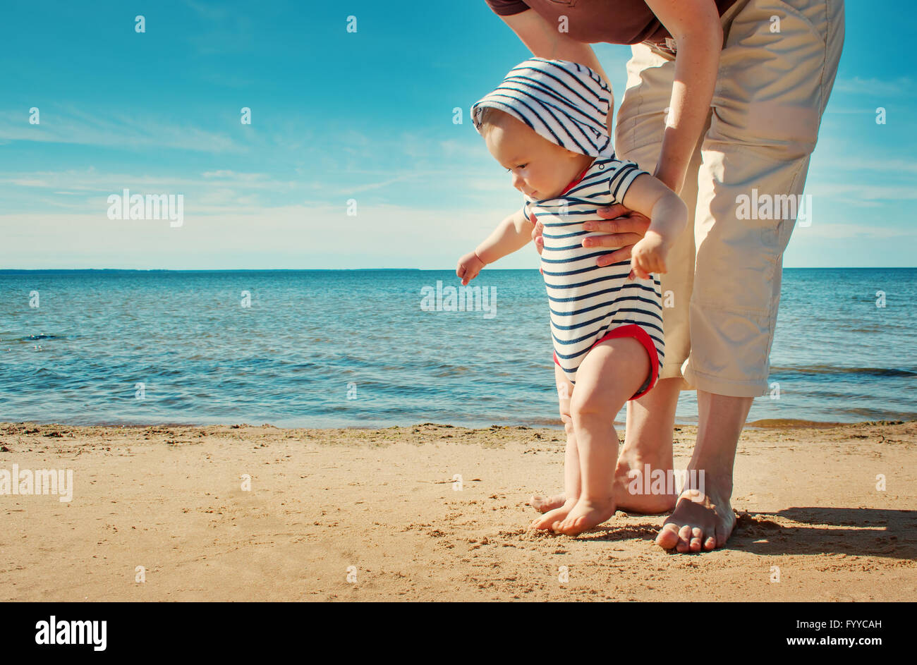 Little baby boy walking on the beach in summer day - Stock Image