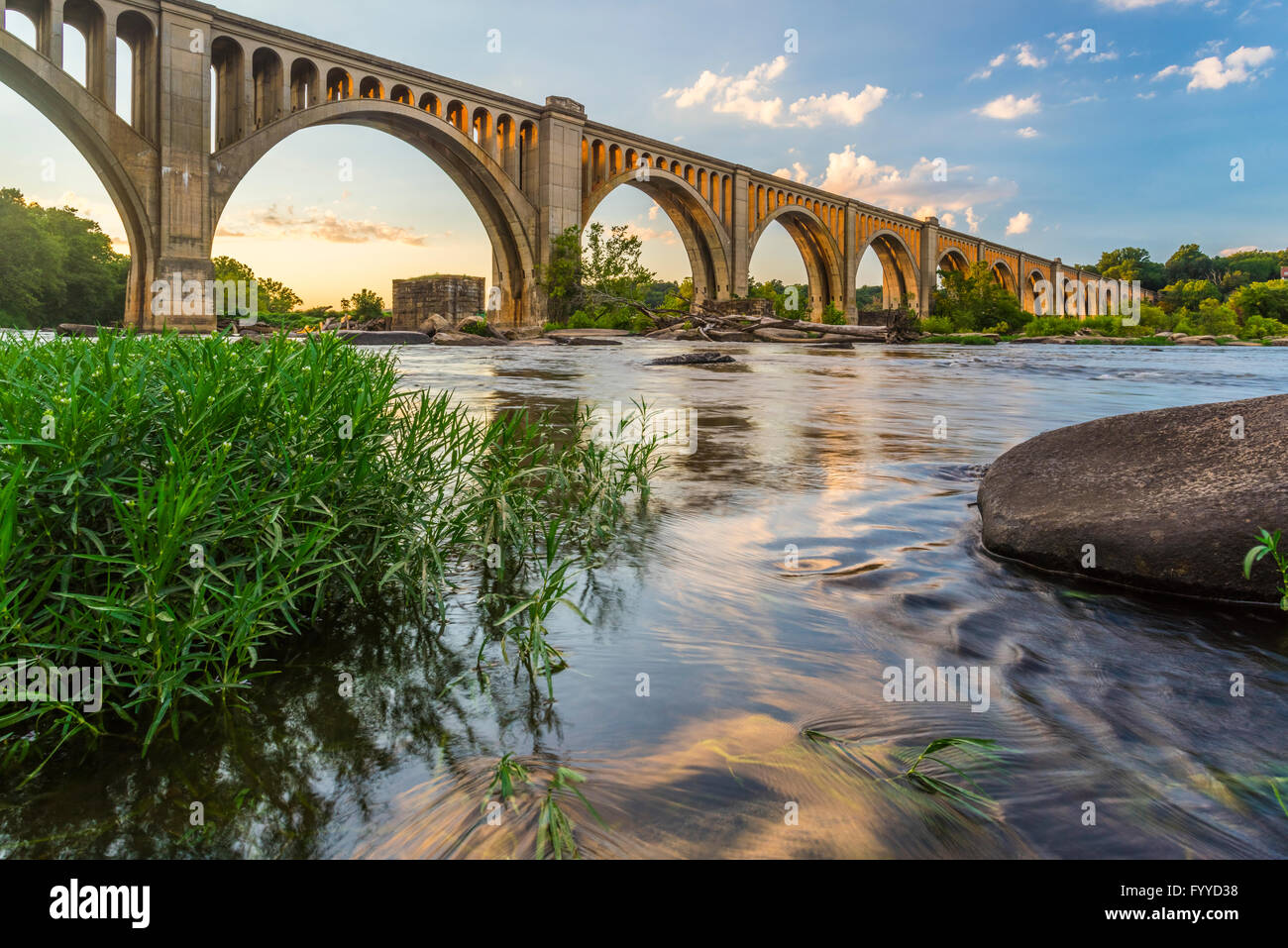 A graceful concrete arch bridge spans the James River near Richmond, Virginia, USA. Stock Photo