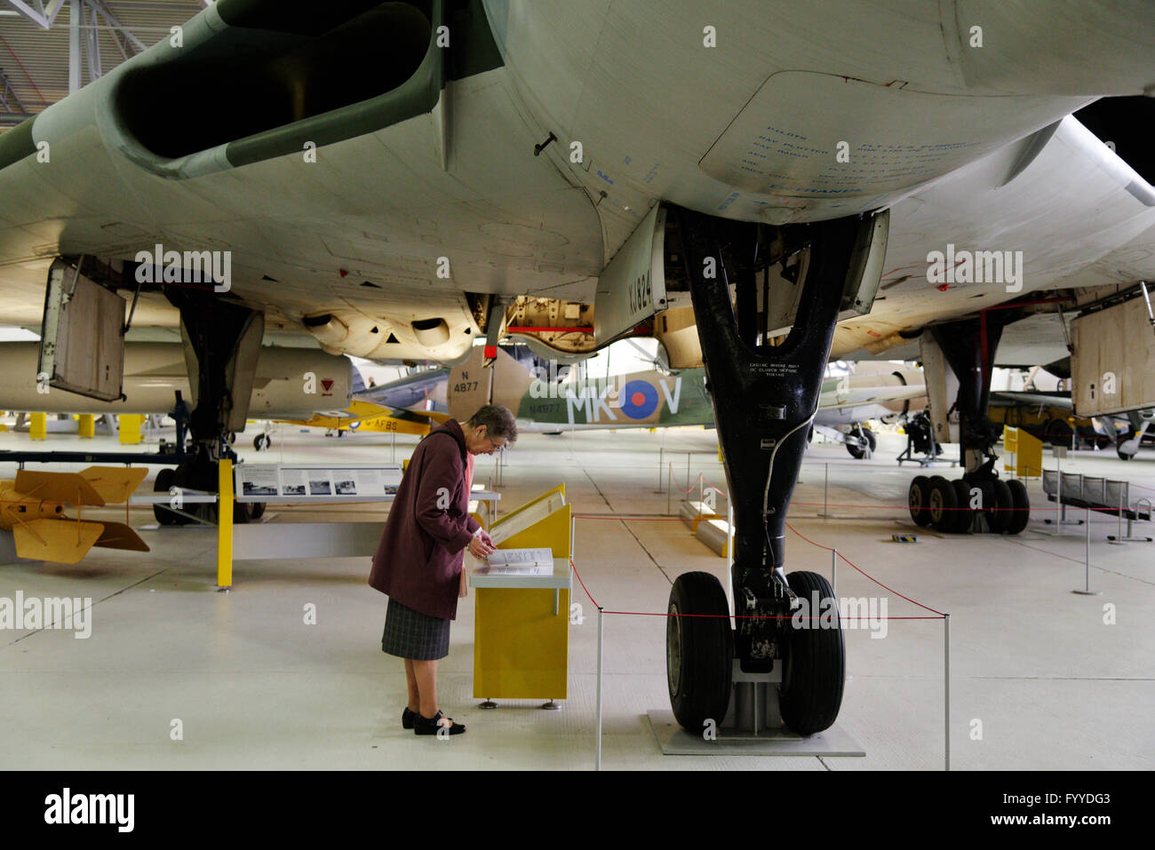 An older lady reading about, and dwarfed by, the Avro Vulcan bomber at Duxford Air Museum, England - Stock Image