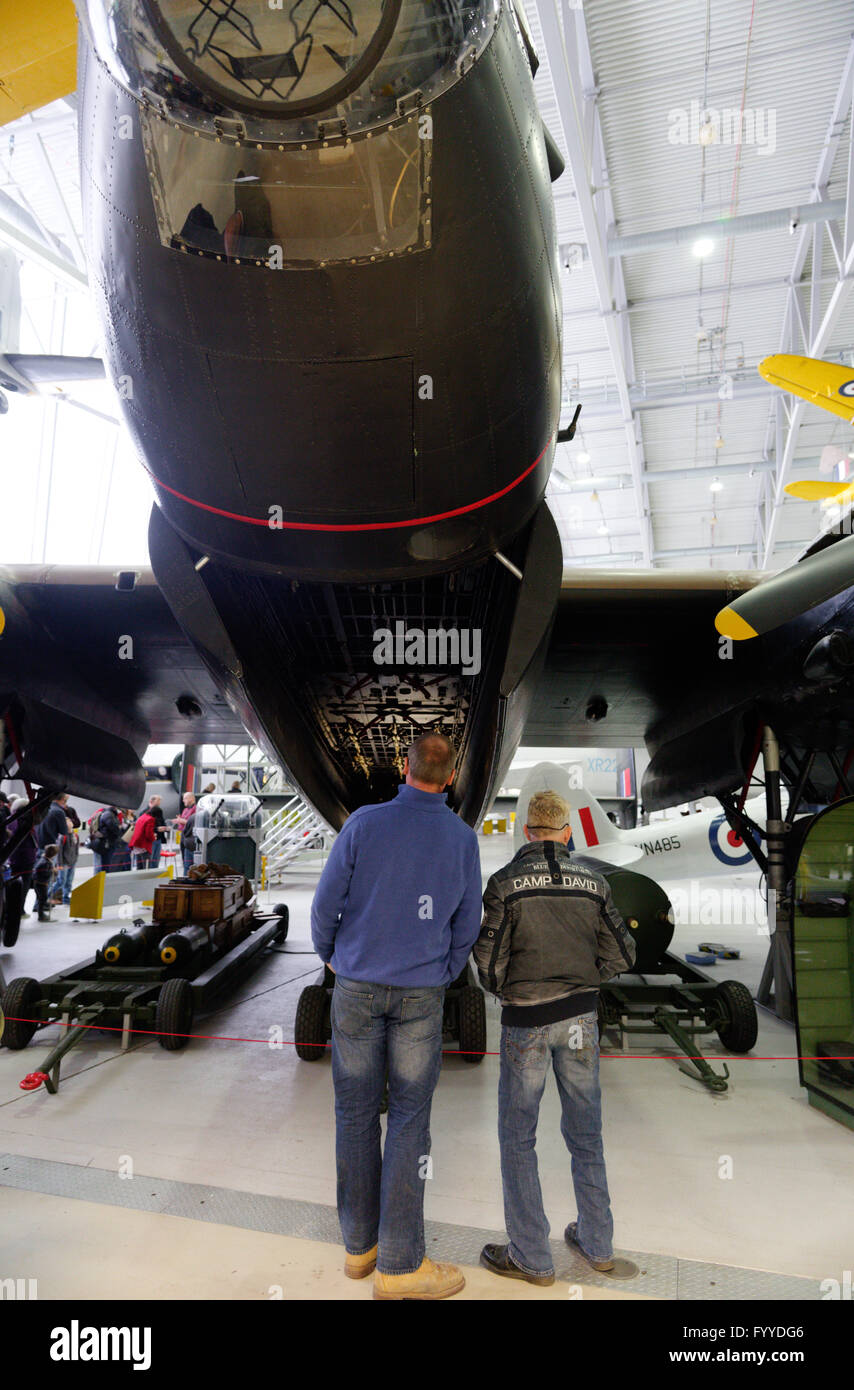 Two men looking at the Avro Lancaster at Duxford Air Museum, England - Stock Image