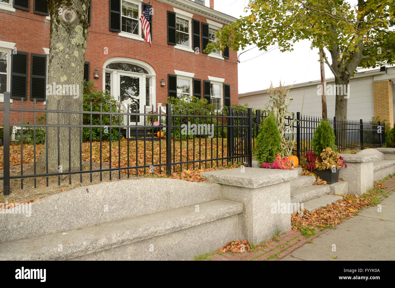 a black wrought iron fence by a red brick colonial style house Stock