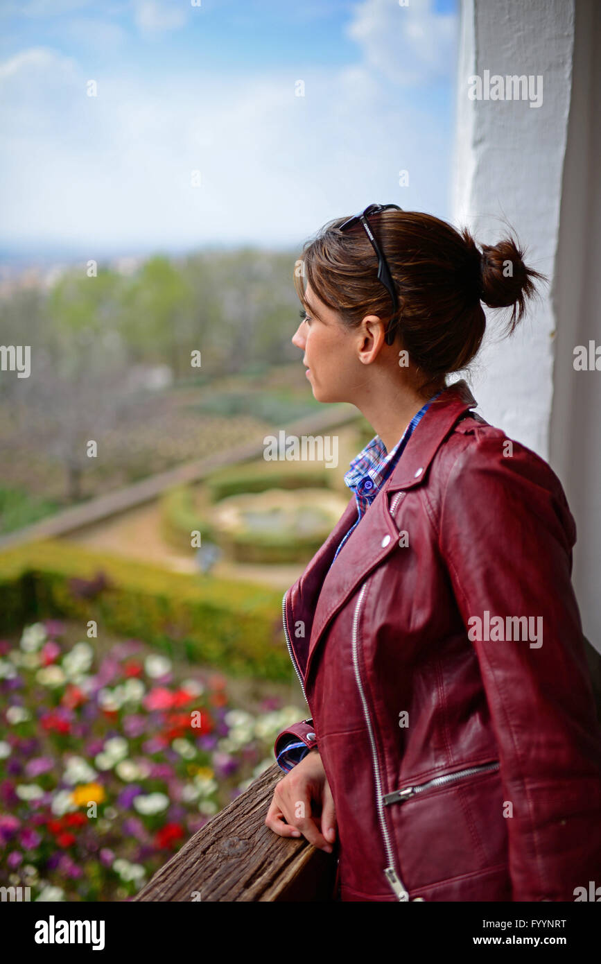 Young woman visiting the Alhambra, palace and fortress complex located in Granada, Andalusia, Spain - Stock Image