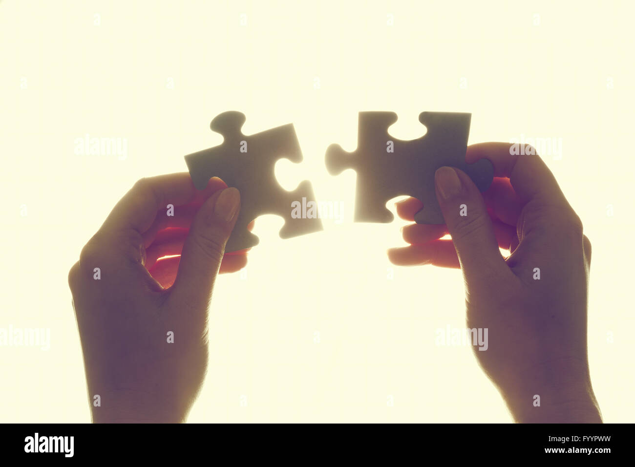 Joining two pieces of jigsaw puzzle. Backlit - Stock Image