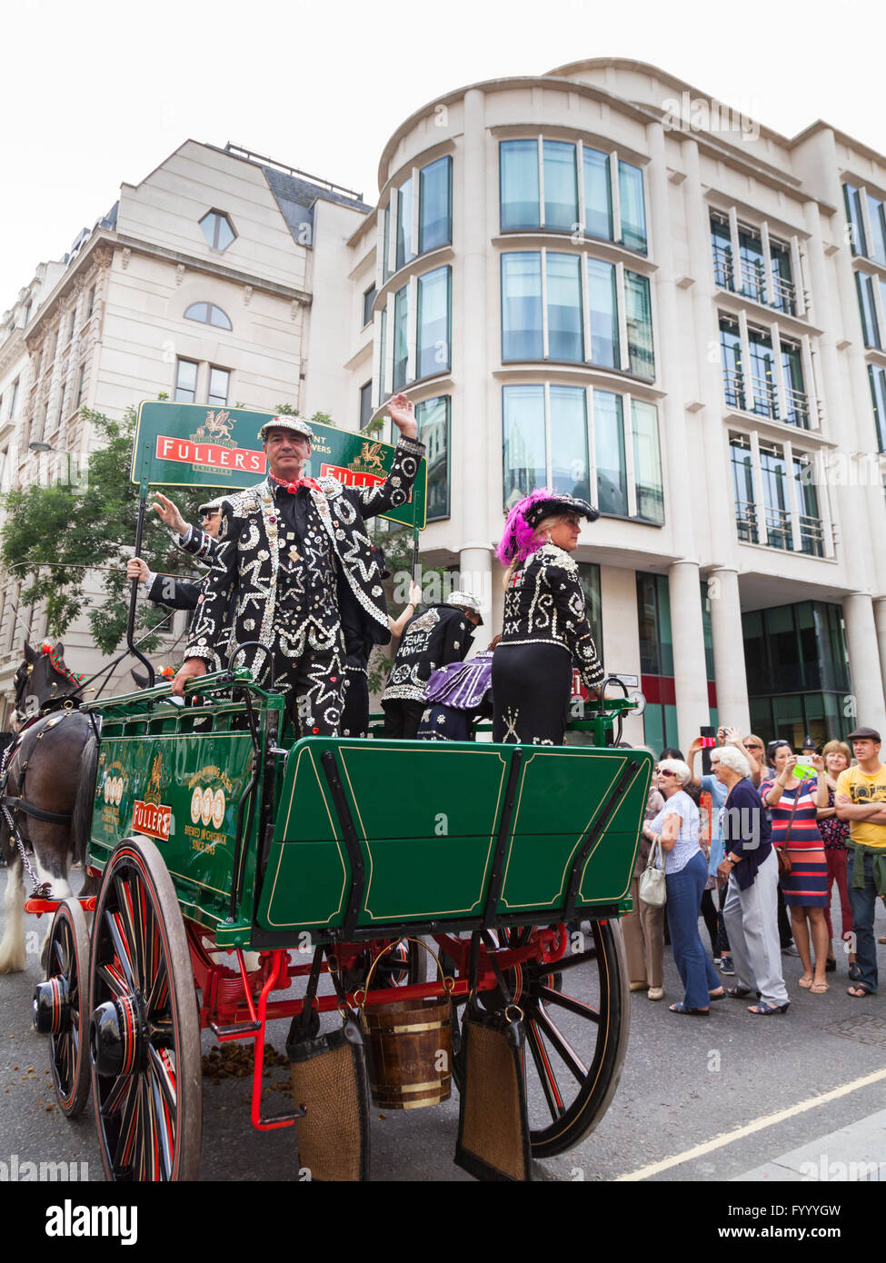 Shaun Austin, the Pearly King of Tower Hamlets, waves from an old Fuller's brewery wagon at the annual Pearly - Stock Image