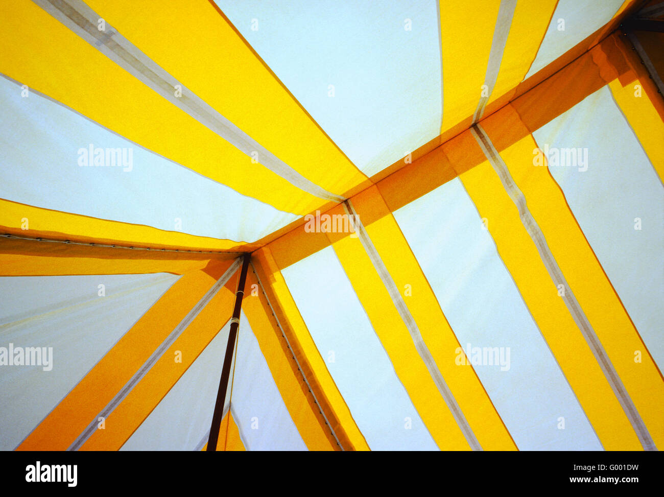 Graphic abstract view of the inside of a large yellow & white event tent - Stock Image