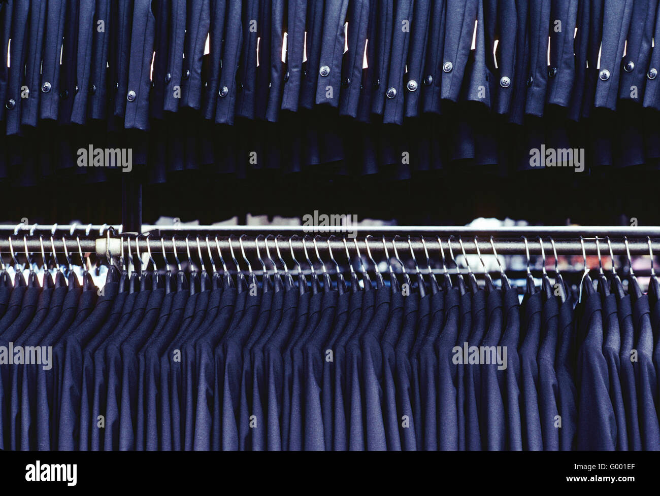 Rows of new tuxedos on a rack in a garment manufacturing facility - Stock Image