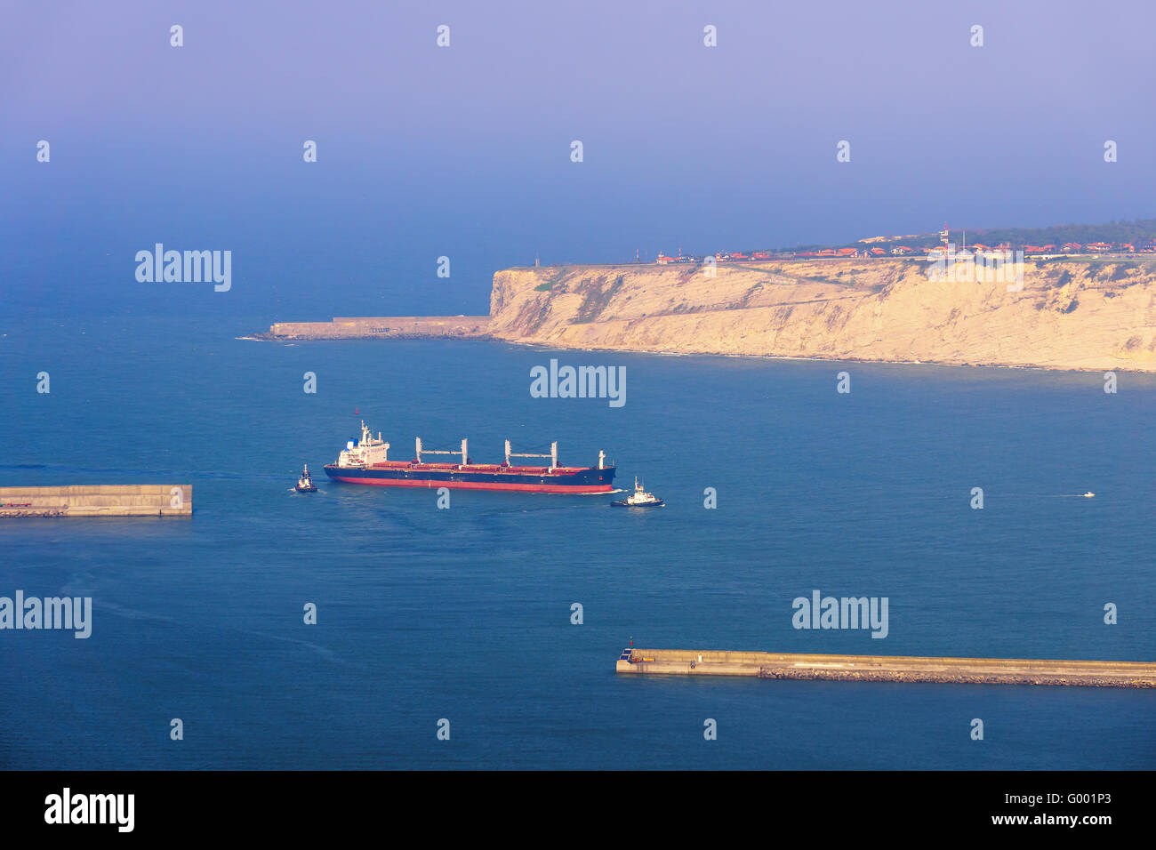 oil tanker ship entering at the bilbao harbor with tugboat assistant - Stock Image