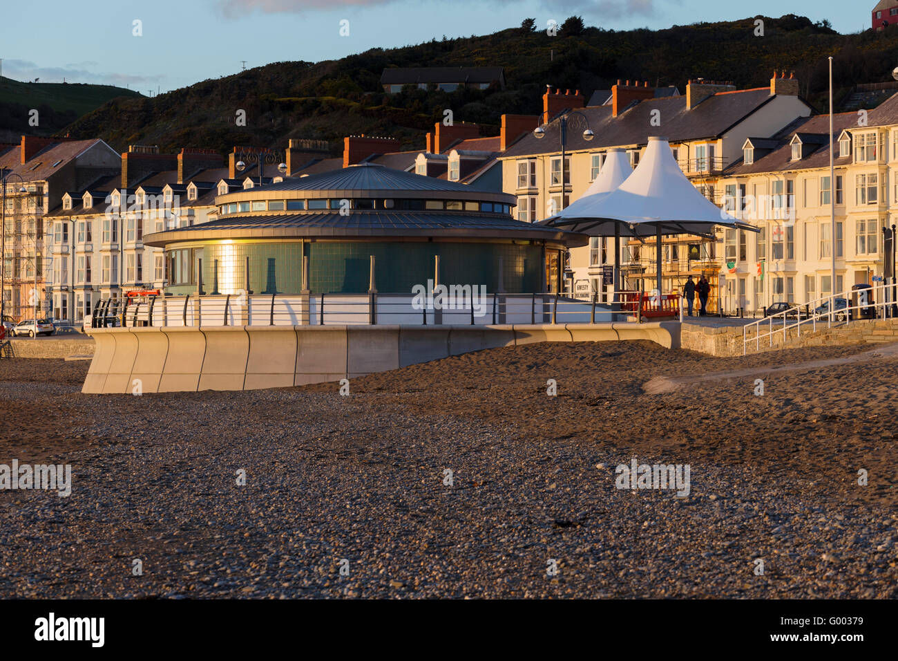 The new Aberystwyth Bandstand lit up by the evening sun, taken from the beach to the south. - Stock Image