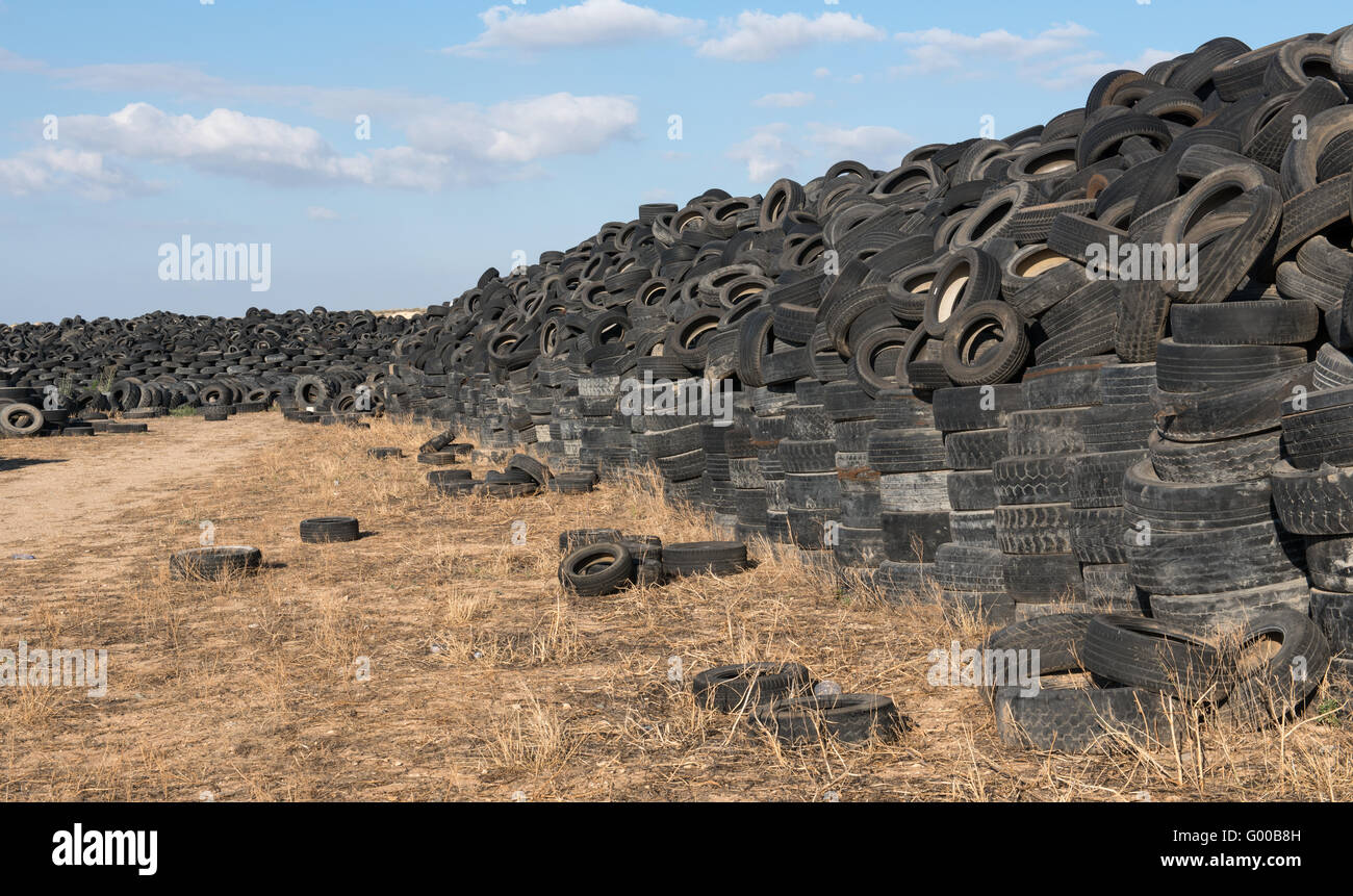 Old  used rubber tires  piled  in a recycling yard waiting to be  shredded and  remanufactured into usable  products - Stock Image