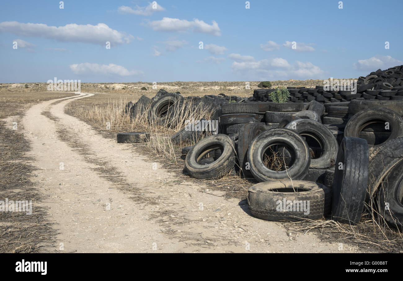 Old  used rubber tires  piled  in a recycling yard waiting to be  shredded and  re-manufactured into usable  products - Stock Image