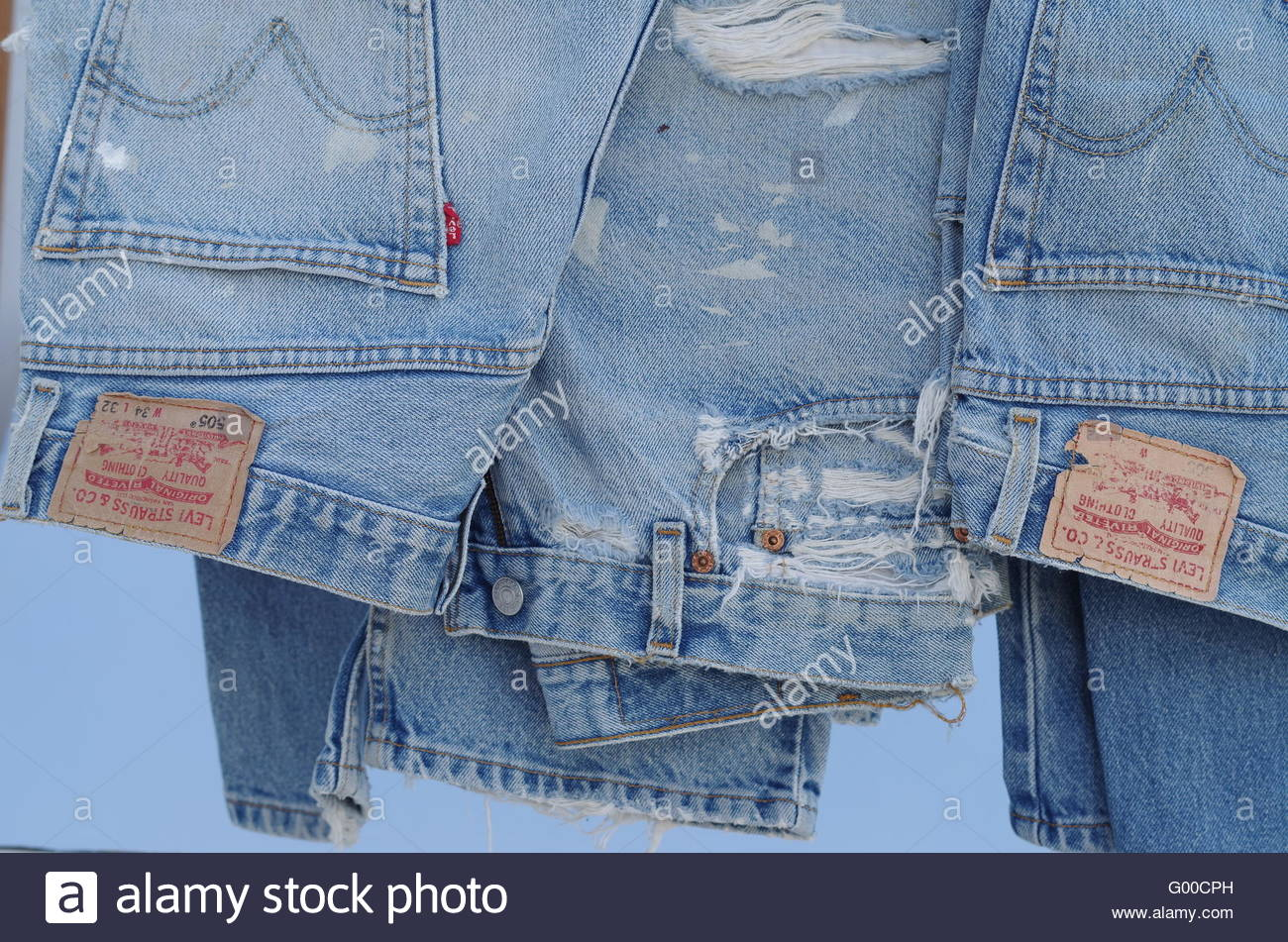 Studio shots closeup old well worn torn frayed Levi 505 jeans showing labels and tags natural light with zippers - Stock Image