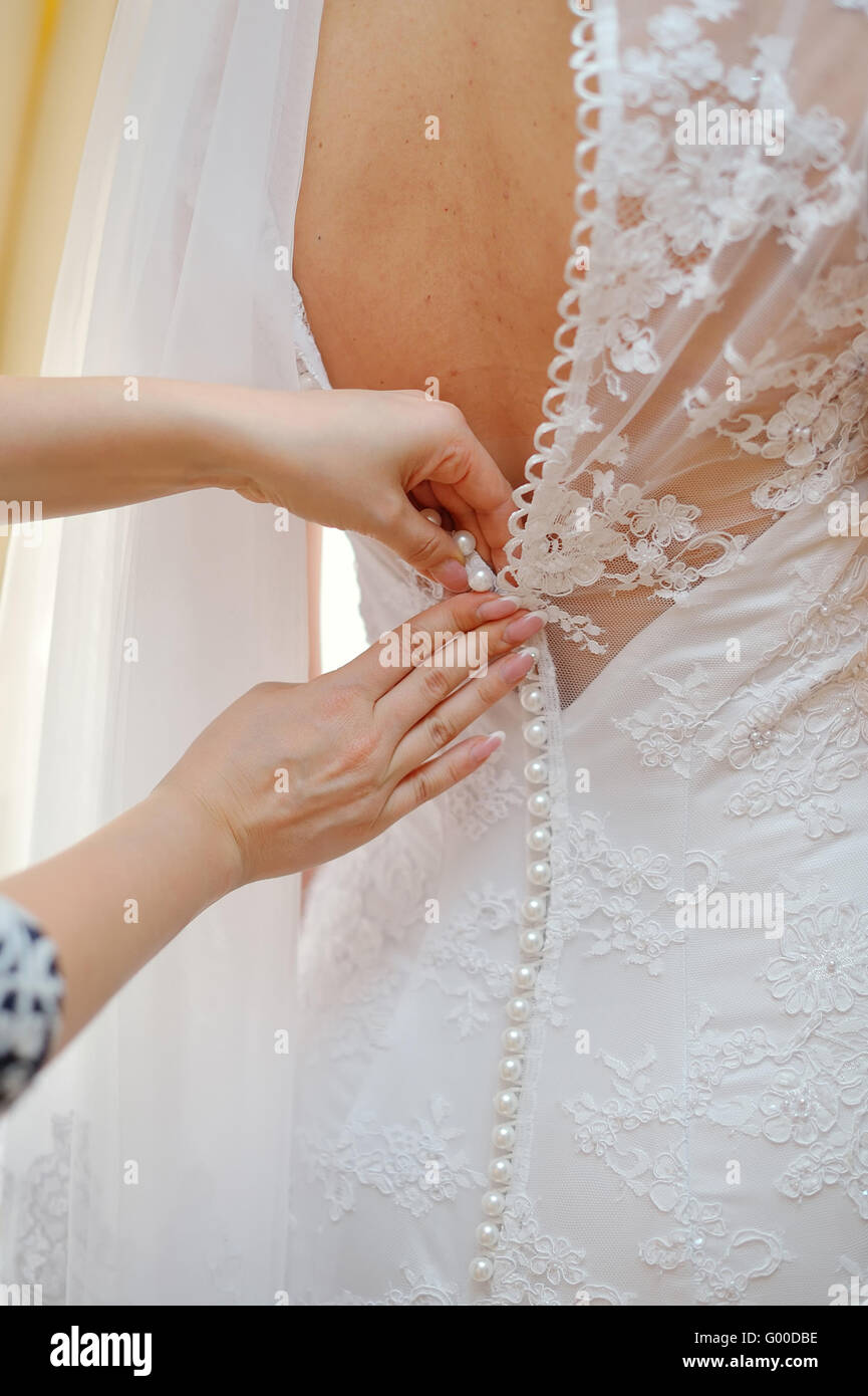 0b22f52fb closeup portrait of a maid of honor helping the bride with her dress - Stock  Image