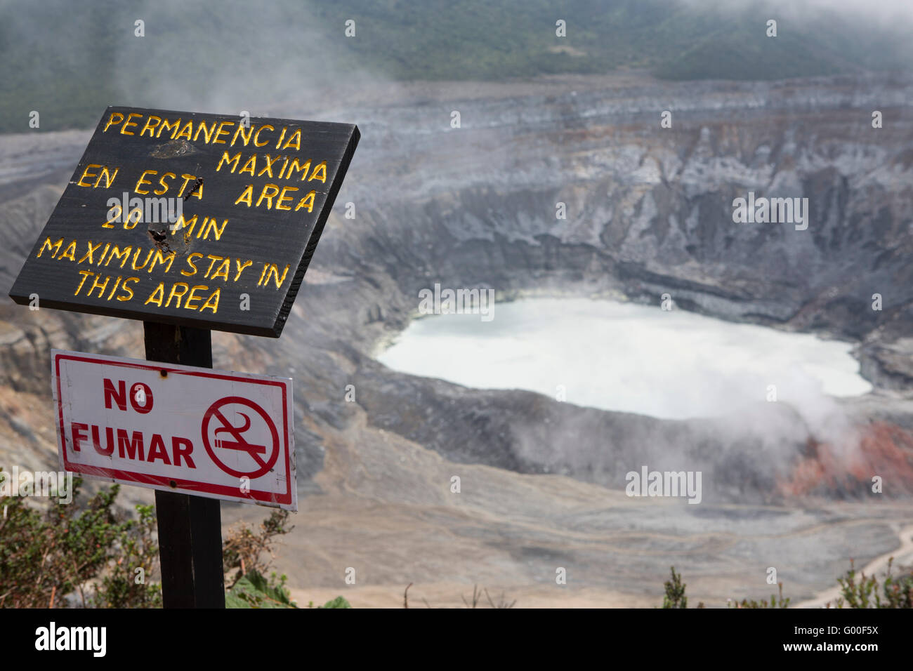 A sign warns visitors not to stay more than 20 minutes by the crater of Poas Volcano in Costa Rica. - Stock Image
