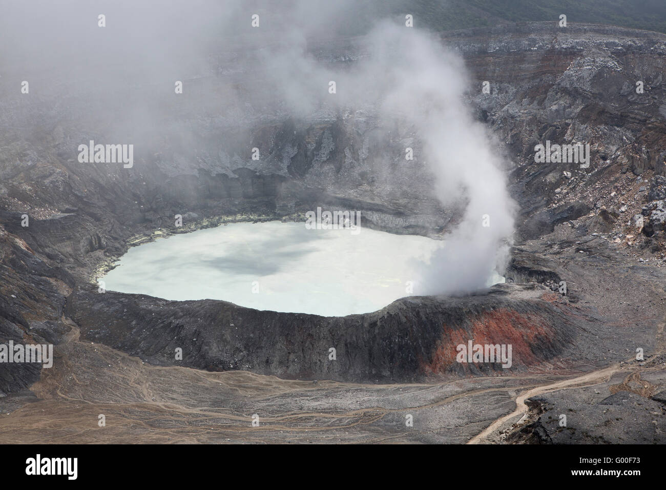 Steam rises from the crater of Poas Volcano in Parque Nacional Volcan Poas (Poas Volcano National Park) in Costa - Stock Image