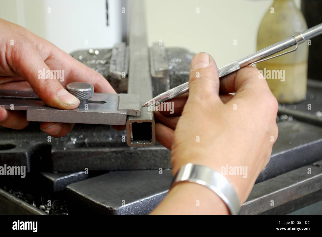 metalworker measuring a metal piece for drilling - Stock Image