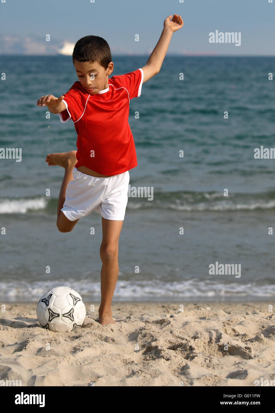 boy playing soccer on the beach - Stock Image