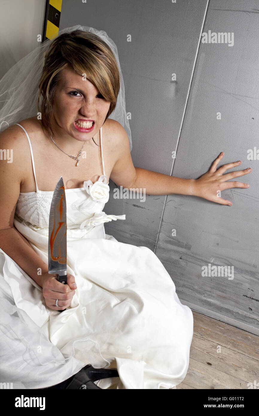 angry young bride with a bloody knife in an elevator - Stock Image