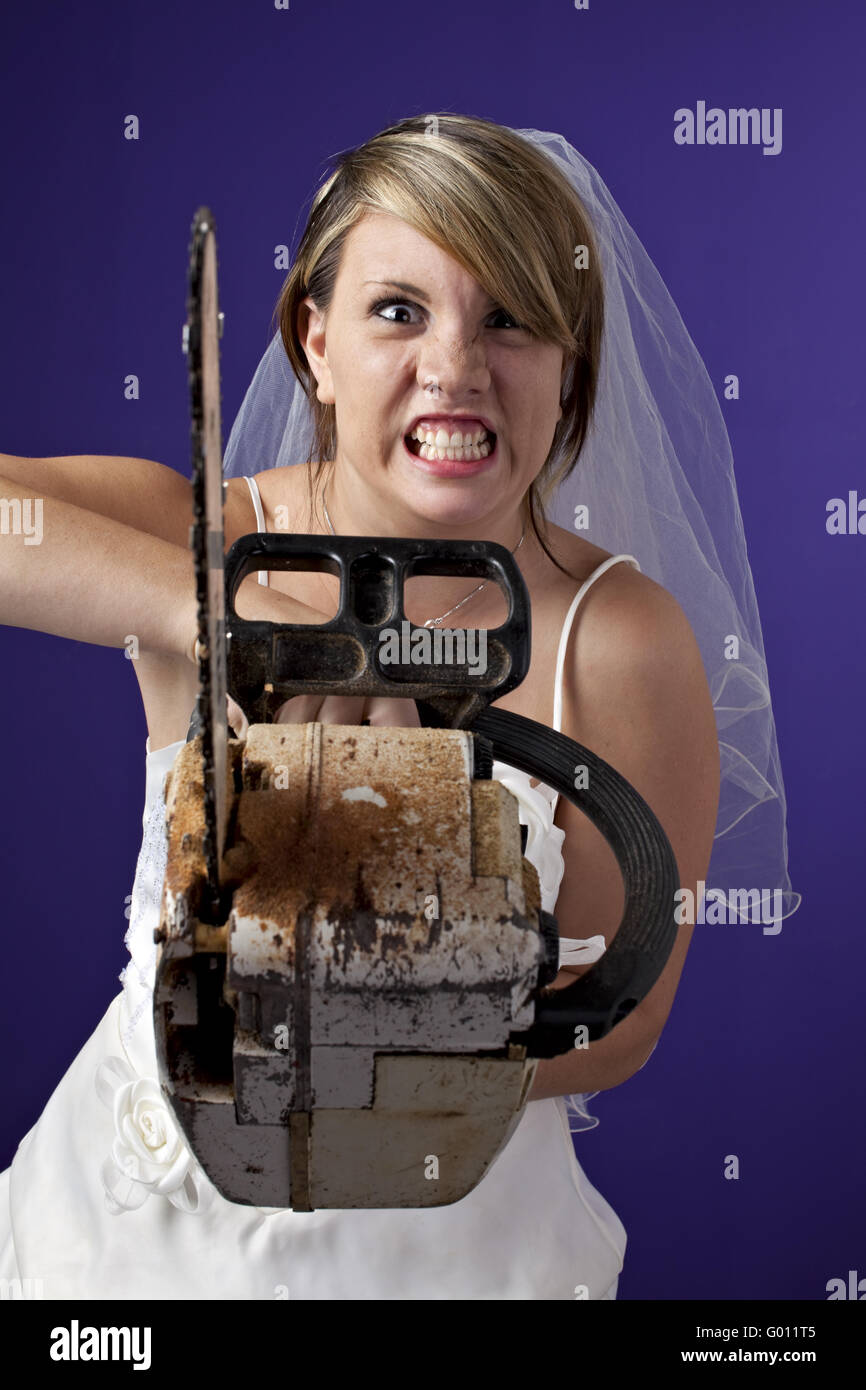 angry young bride with an chainsaw on a dark blue background - Stock Image