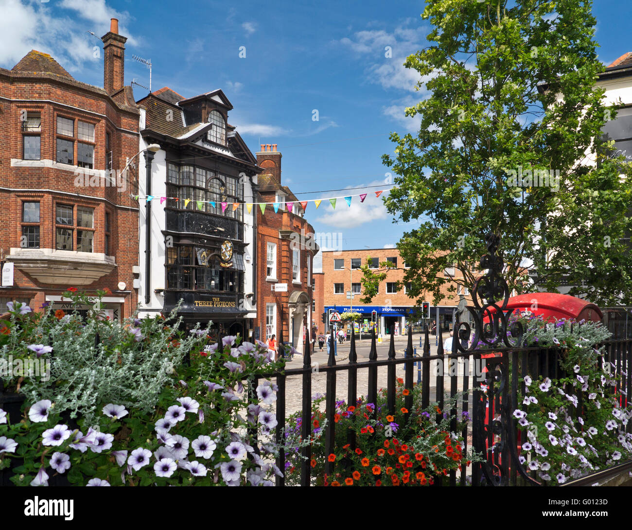 Guildford High Street with petunias and traditional red telephone box Three Pidgeons public house Guildford Surrey - Stock Image