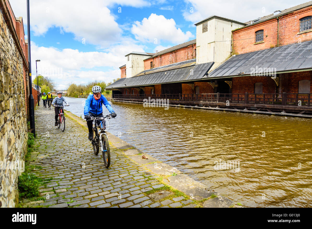 Cyclists on towpath of Leeds and Liverpool Canal opposite Wigan Pier in Wigan Greater Manchester UK - Stock Image