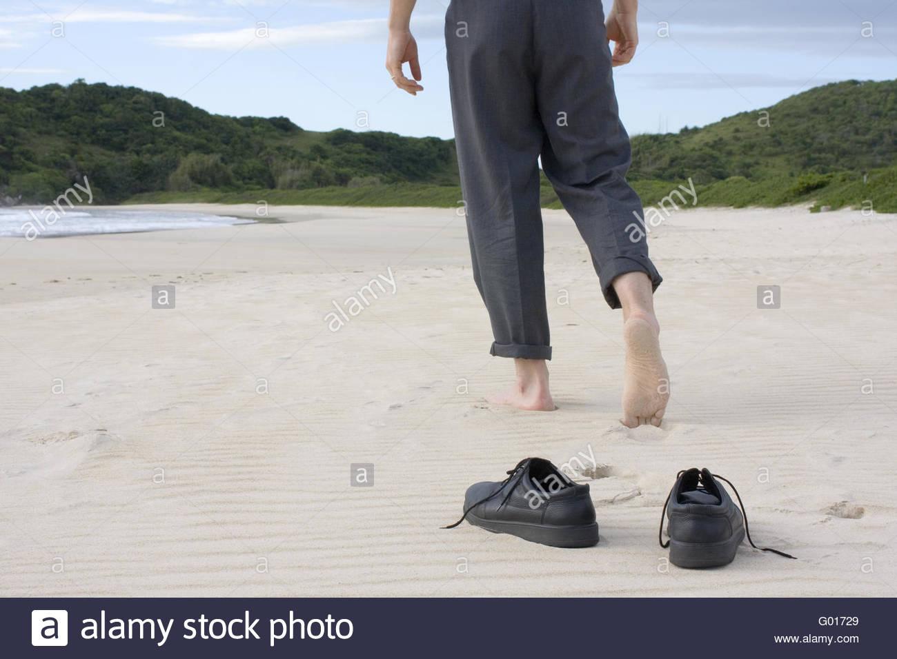 Businessman barefoot on beach Stock Photo