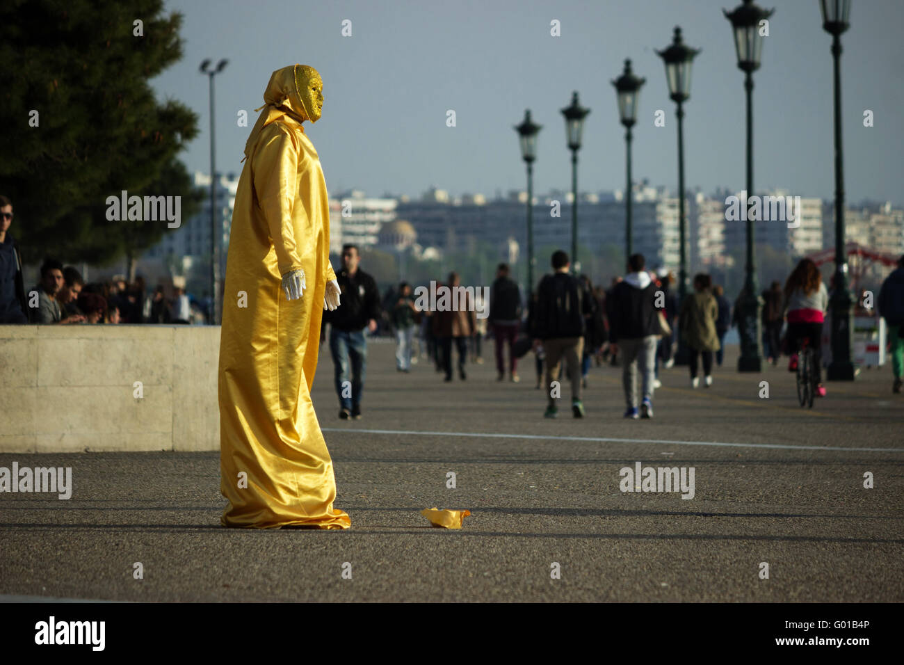 A street busker mime artist wearing a gold reflective sequin dress working for gratuities on Salonika's New - Stock Image