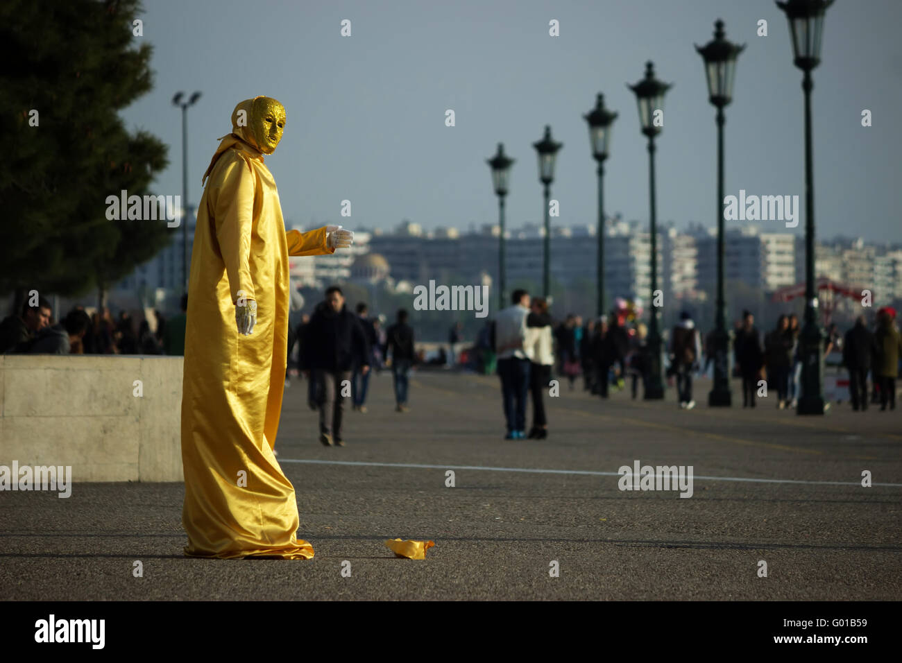 A street mime artist wearing a gold sequin dress performing live on Thessaloniki's waterfront, near White Tower. - Stock Image