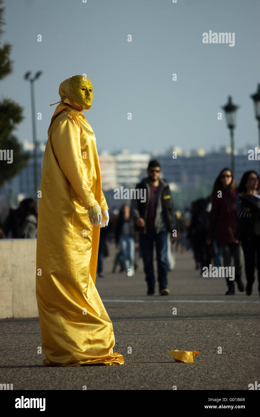 Close view of a street mime artist standing at the New promenade of Thessaloniki, wearing a gold sequin dress. Thessaloniki - Stock Image