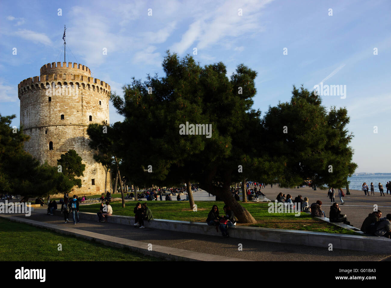 The White Tower landmark of Thessaloniki or Thessalonica and people having a break at the New promenade's park. - Stock Image