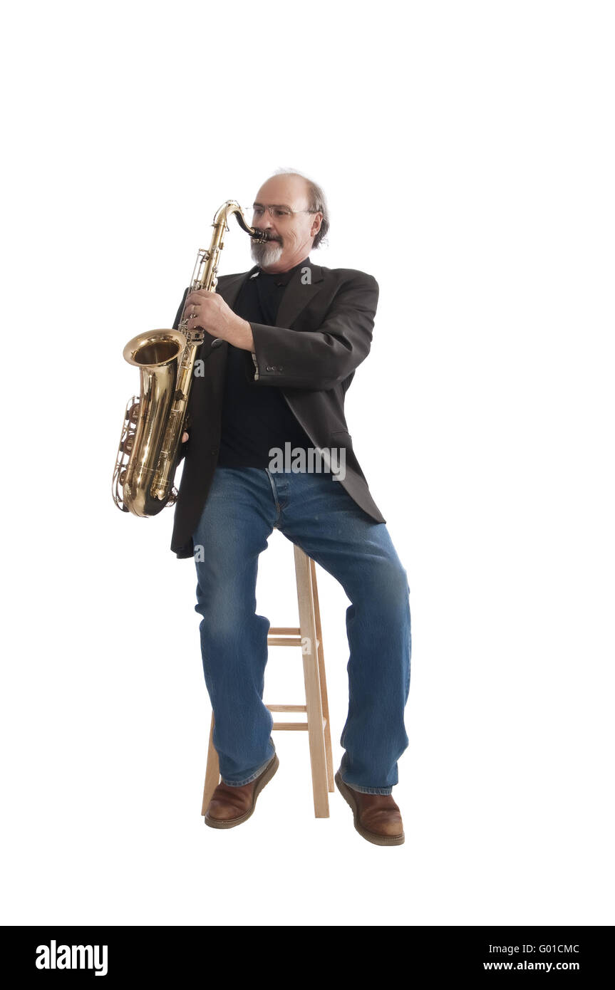 Playing a tenor sax seated on a stool - Stock Image
