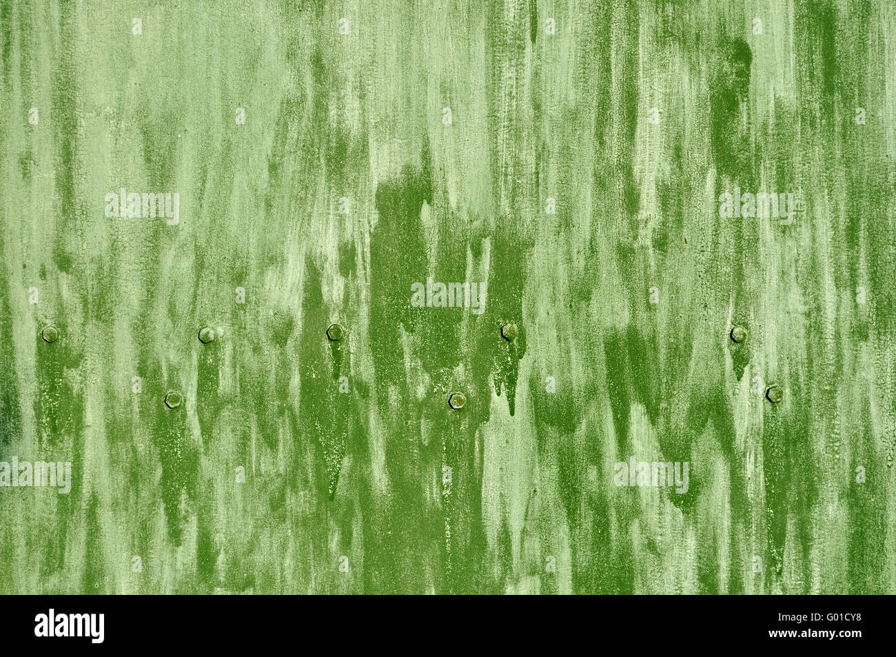 Close up of rough green colored metal background with bolts - Stock Image